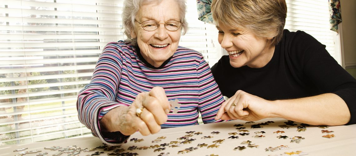 Elderly woman and a younger woman work on a jigsaw puzzle.